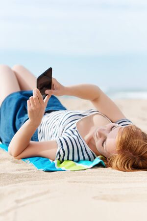 Relaxed young woman looking at mobile phone at the beach photo