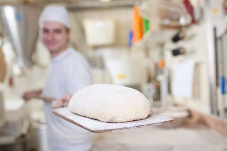 Baker preparing a handmade loaf of bread getting ready to place it into the ovens to bake photo