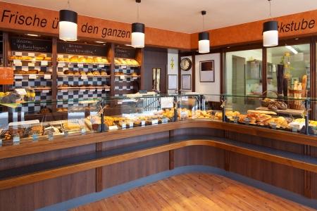 Interior panadería moderna con pantalla contadores de vidrio llenos de pan delicioso y pasteles