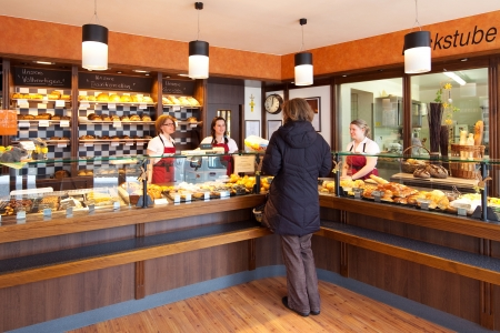 Customer in a modern bakery standing at a fully stocked counter display being attended to by friendly staff
