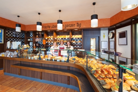 food stores: Interior view of a fully stocked specialist bakery with long display counters and a group of friendly staff standing behind the counter