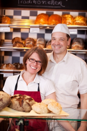Friendly bakery staff standing behind the counter in a modern bakery with well stocked shelves photo