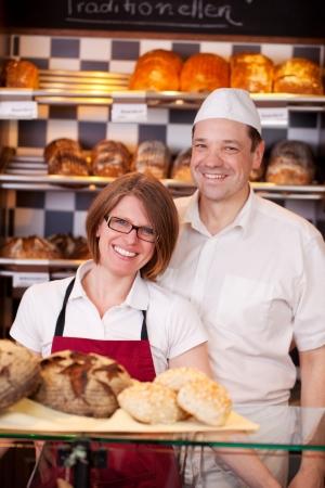 negocios comida: Personal agradable panader�a de pie detr�s del mostrador de una panader�a moderna con estantes bien surtidos