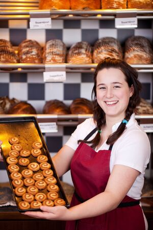 saleslady: Smiling bakery assistant displaying a tray with freshly baked biscuits as she stands inside a bakery serving clients