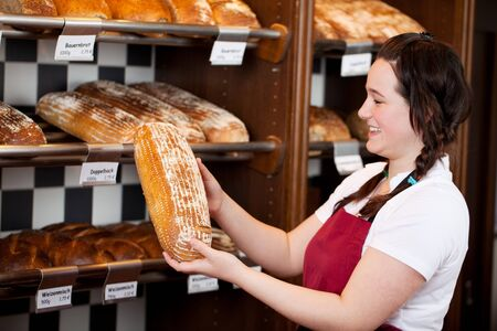 saleslady: Bakery worker with a loaf of fresh crusty bread in her hands which she is displaying after removing it from the shelf Stock Photo