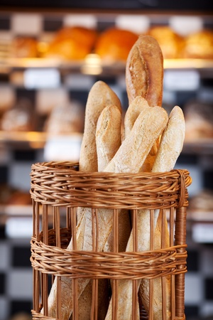 Crusty fresh baked bread loves standing on display in a wicker basket in the bakery photo