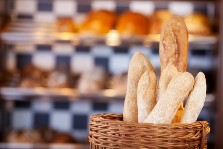 Fresh baguettes in a bakery standing in a wicker basket on the counter photo