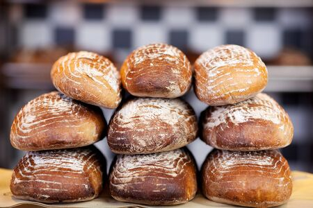 bakery products: Stack of freshly baked loaves of crusty bread on a countertop in a bakery
