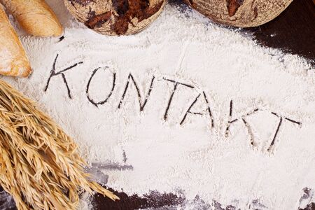 write us: The word Kontakt, written in flour on bakery table