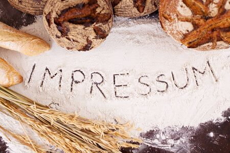 The word 'Impressum', written in flour surrounded by a variety of bread loaves photo