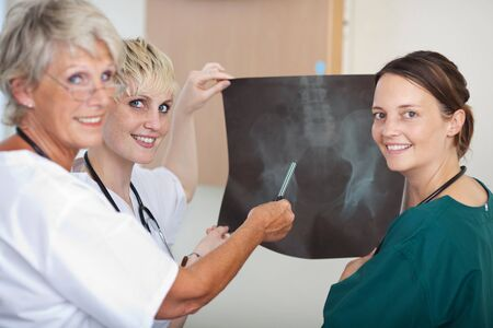 Portrait of confident medical team of female doctors analyzing Xray report together in clinic photo