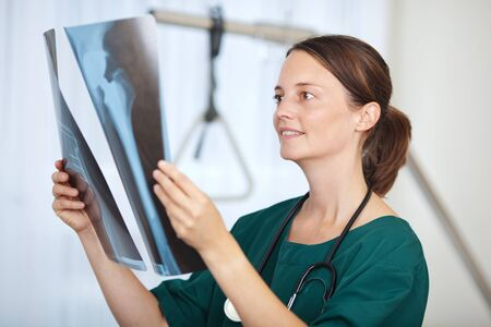 Portrait of female doctor holding hip Xray report in hospital photo