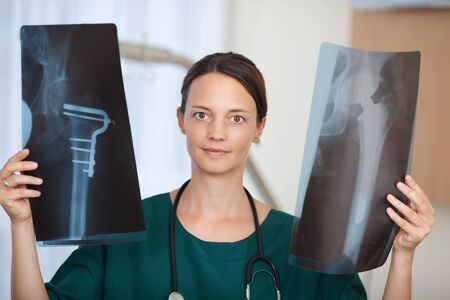 Portrait of confident female doctor holding Xray reports in hospital photo
