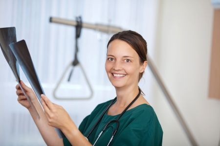 Portrait of confident smiling female doctor holding Xray reports in hospital photo