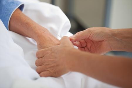 bedside: Female doctor adjusting drip on patients hand in hospital