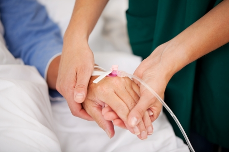 Closeup of nurse holding patients hand in hospital photo