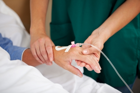 infusion: Female doctor checking patients pulse in hospital Stock Photo