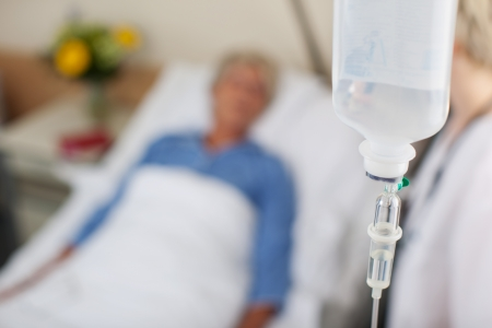 Closeup of infusion bottle with patient and doctor in hospital