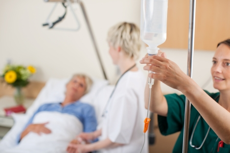 Nurse adjusting infusion bottle with doctor and patient in background in hospital Imagens