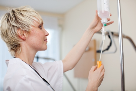 Female doctor adjusting infusion bottle in hospital photo