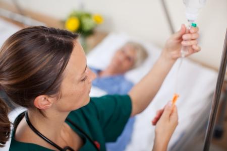Vrouwelijke arts aanpassing infusiefles met patiënt liggend op bed in het ziekenhuis Stockfoto