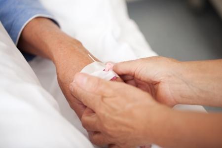 nursing treatment: Detalle de la enfermera femenina ajustando goteo en mano de los pacientes en el hospital
