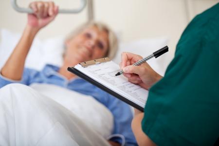 bedside: Mediados enfermera hembra adulta escrito en el portapapeles mientras mira a los pacientes en el hospital