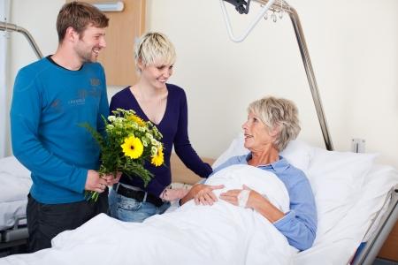 ni�os enfermos: Ni�os felices con flores visitando madre en el hospital Foto de archivo
