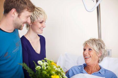 visitador medico: Niños felices con el ramo de flores visitando madre en el hospital