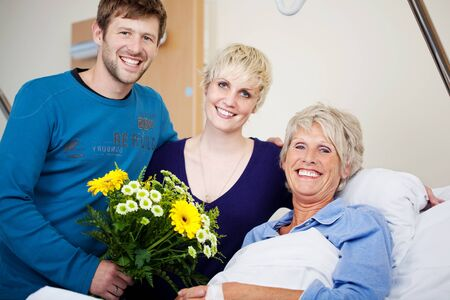 recovering: Happy male and female with flower bouquet visiting mother in hospital Stock Photo