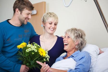 visitador medico: Los niños con ramo de flores de visita feliz madre en el hospital Foto de archivo