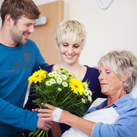 empatia: Ni�os felices que da el ramo de flores a la madre en el hospital Foto de archivo