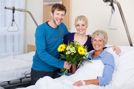 Portrait of happy children giving bouquet to mother in hospital photo