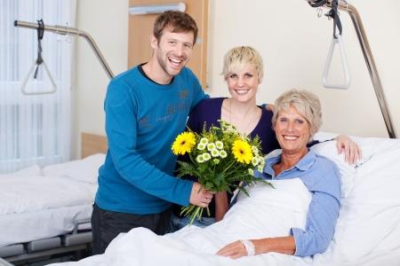 visitador medico: Retrato de niños felices dando ramo de flores a la madre en el hospital Foto de archivo