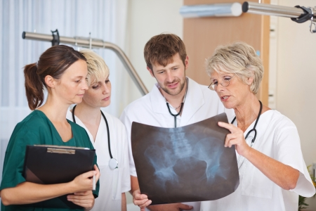 Group of doctors discussing over Xray in hospital photo