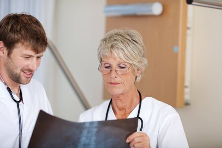 orthopaedic: Portrait of confident male and female doctors looking at Xray report in hospital