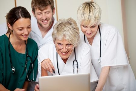 Smiling male and female doctors looking at laptop in hospital photo