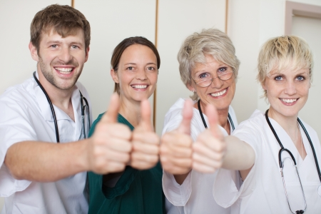 thumbs up group: Portrait of confident doctors team showing thumbs up while standing in a row at clinic Stock Photo