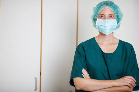 Portrait of female surgeon with arms crossed standing in hospital photo