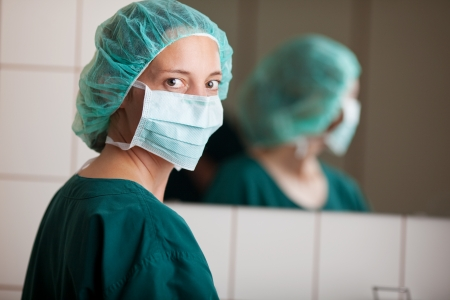 Portrait of female surgeon wearing mask with mirror in background at clinic