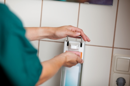 Cropped image of female surgeon using handwash in hospital photo