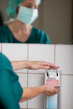desinfectante: Imagen cosechada de la mujer cirujano con lavamanos en el baño