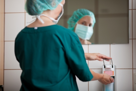 nurse cap: Manos femeninas utilizando dispensador de desinfectante de los médicos en el baño