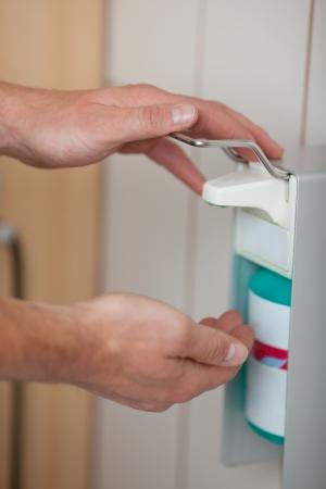 desinfectante: Manos de los médicos con dispensador de desinfectante en el baño
