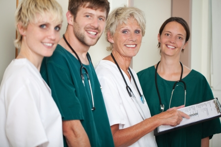 Portrait of happy male and female doctors standing in hospital photo