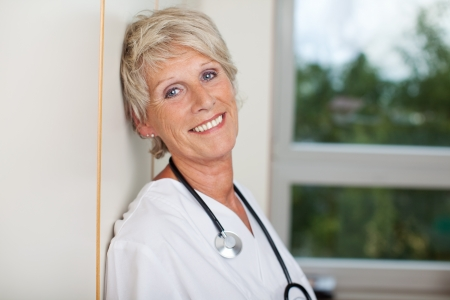 Portrait of smiling senior female doctor against wall in hospital photo