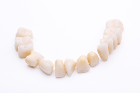 Complete lower dentition of prosthetic teeth isolated on a white background photo