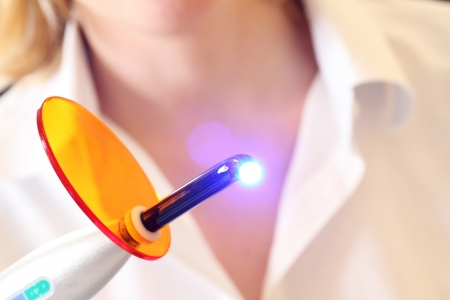 Close-up of a dentist holding a lit dental curing UV light