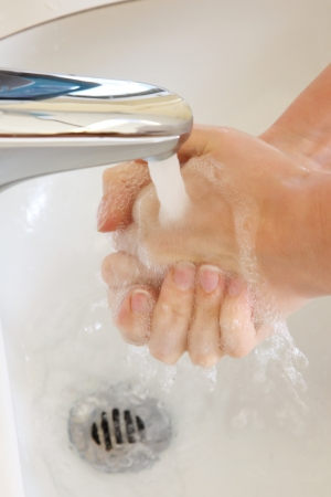 Close-up of hand washing under a tap with running water photo