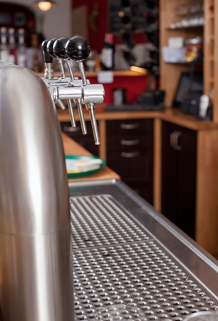 View behind a counter in a bar of the row of metal spigots for dispensing beer and beverages